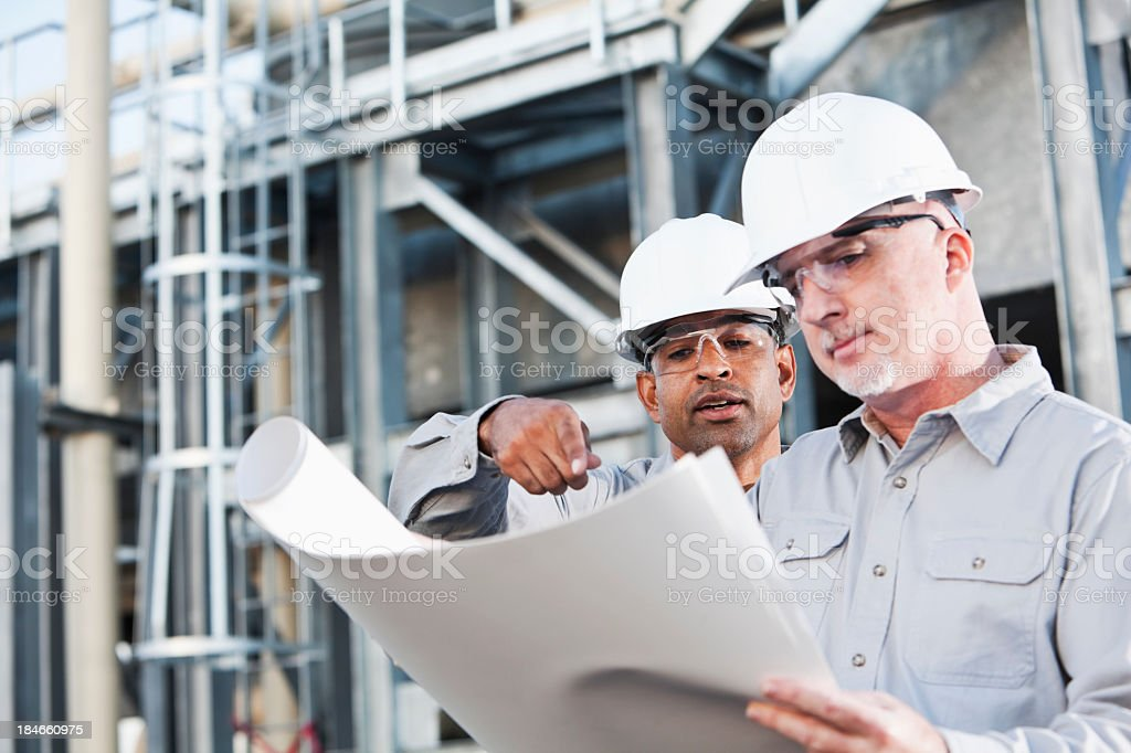 Multiracial engineers at industrial site reading plans stock photo