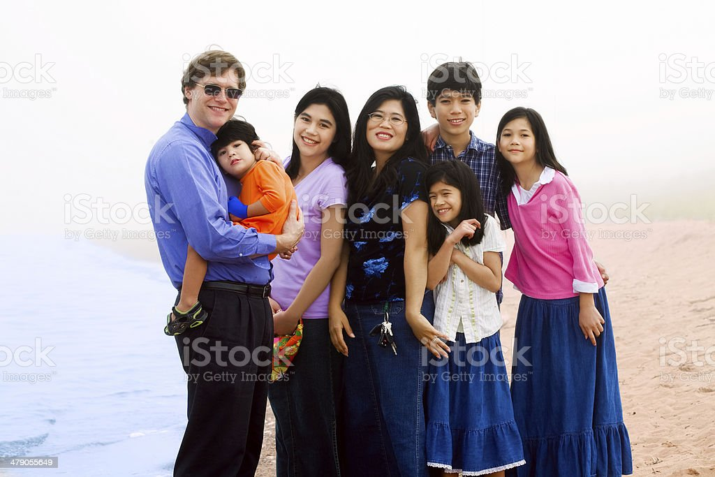 Multiracial family of seven on foggy beach stock photo