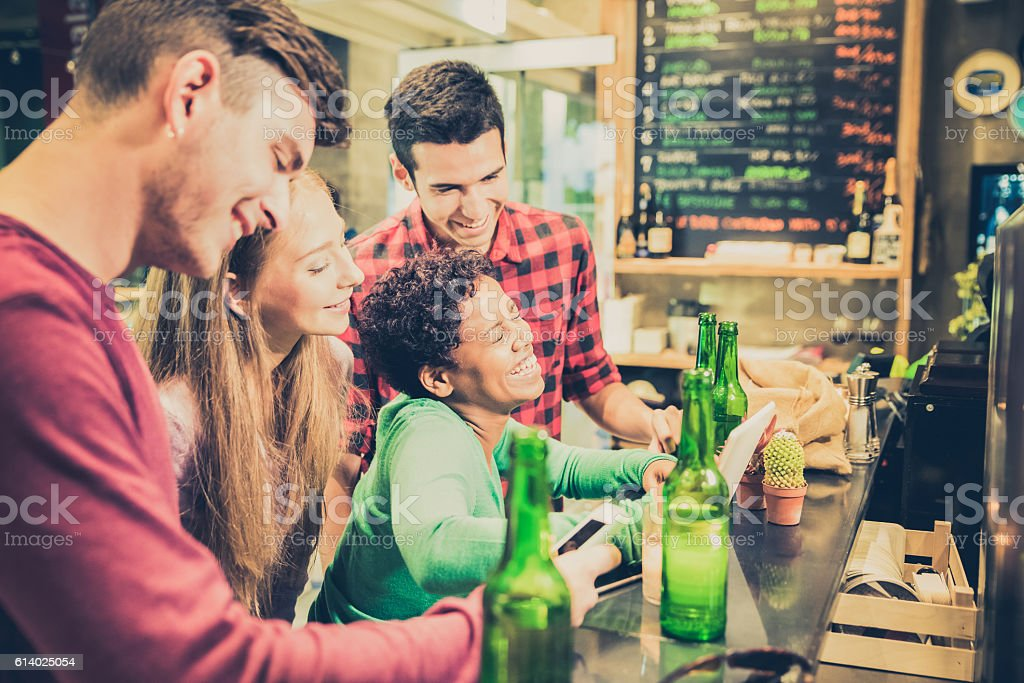 Multiracial friends drinking beer and having fun at cocktail bar stock photo