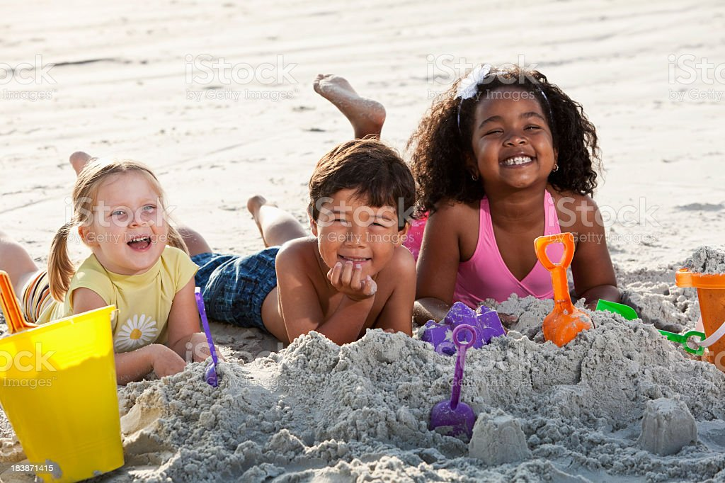 Multiracial friends playing in sand at the beach stock photo