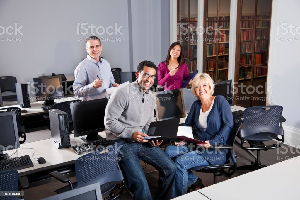 Multiracial group of adults working in computer lab stock photo