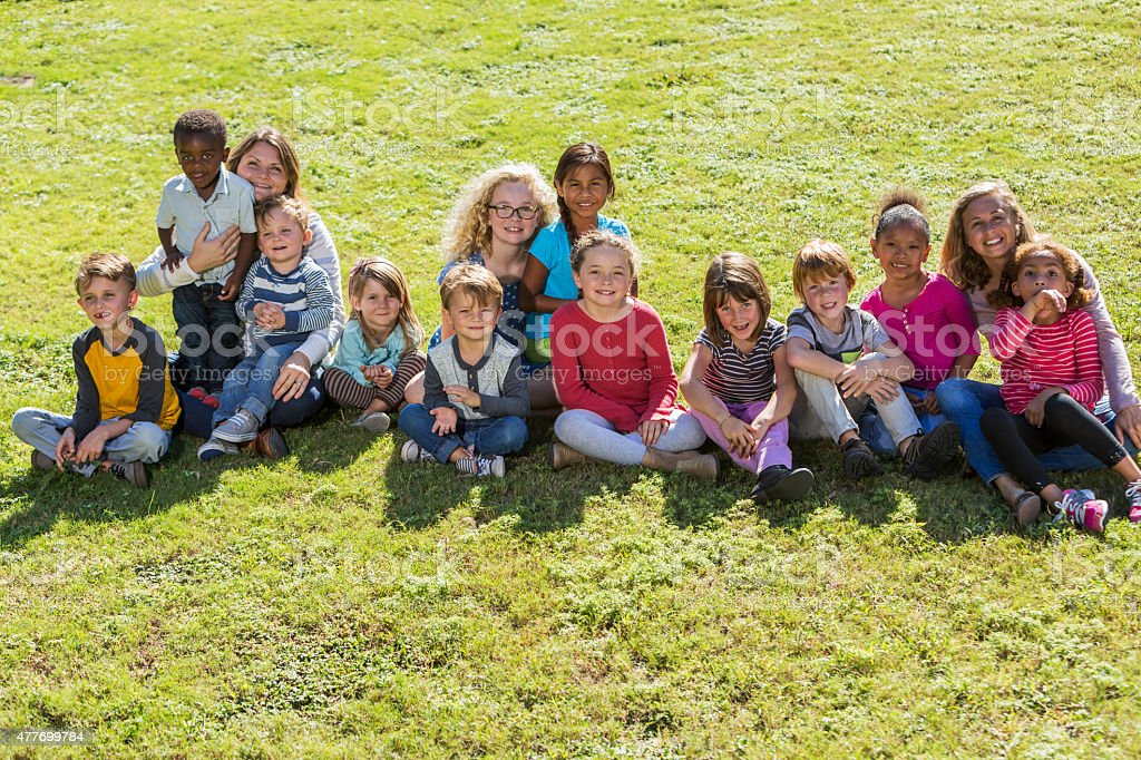 Multiracial group of children with two adults on grass stock photo