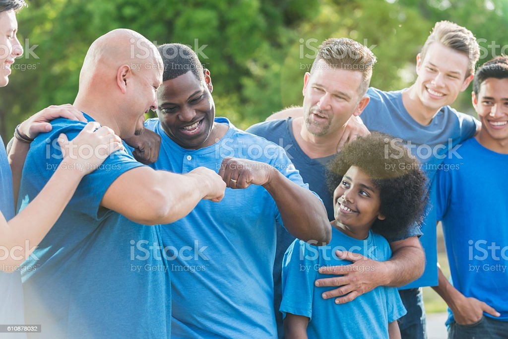 Multi-racial group of fathers and sons in blue shirts stock photo