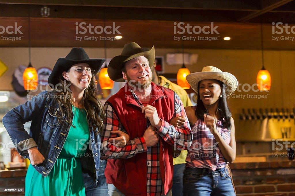 Multiracial group of friends at bar wearing cowboy hats stock photo