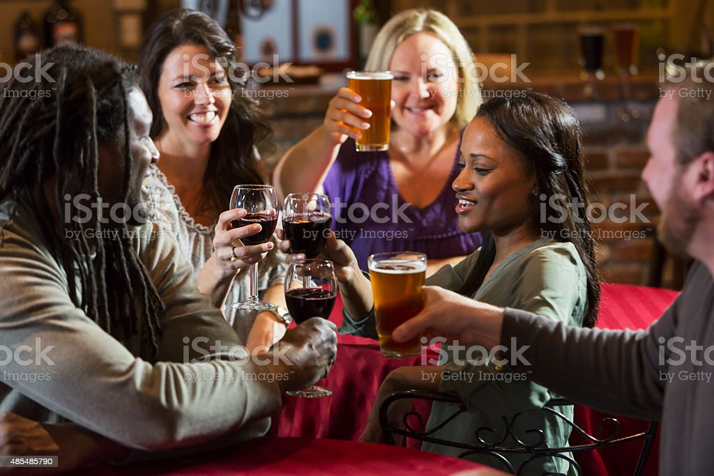 Multiracial group of friends drinking at restaurant bar stock photo