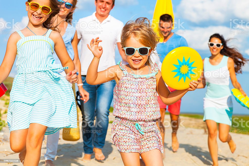 Multiracial group of friends walking at the beach stock photo