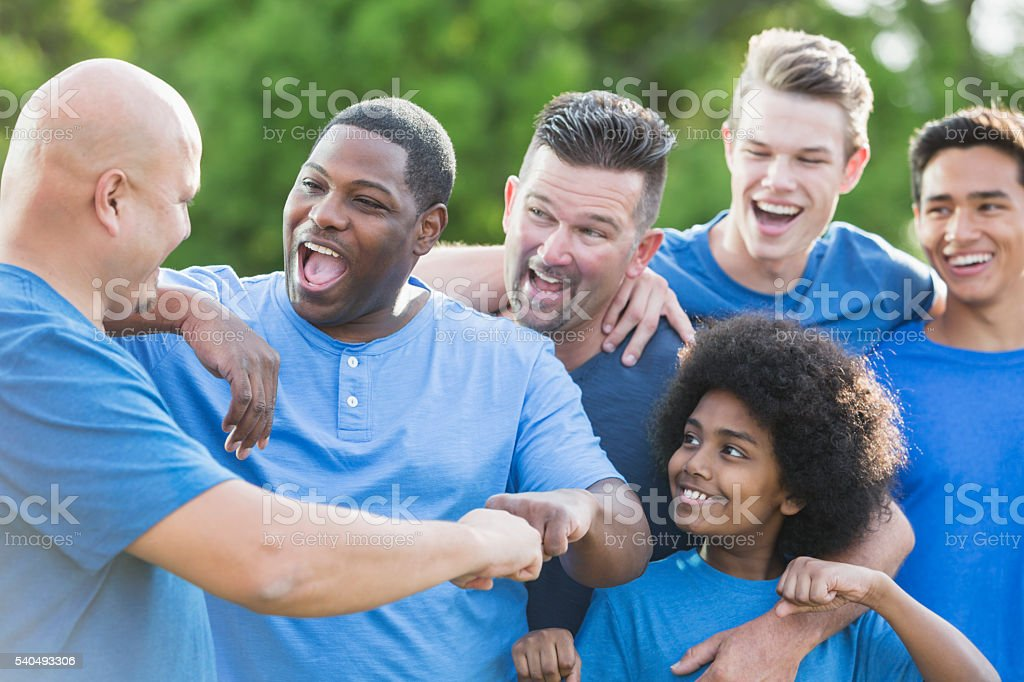 Multi-racial group of men and sons, fist bump stock photo