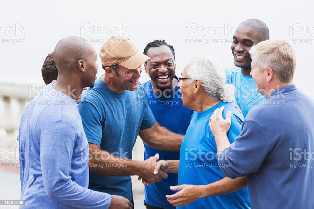 Multi-racial group of men,   shaking hands stock photo