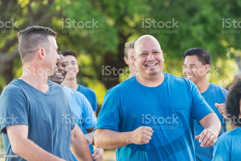 Multi-racial group of men wearing blue shirts stock photo