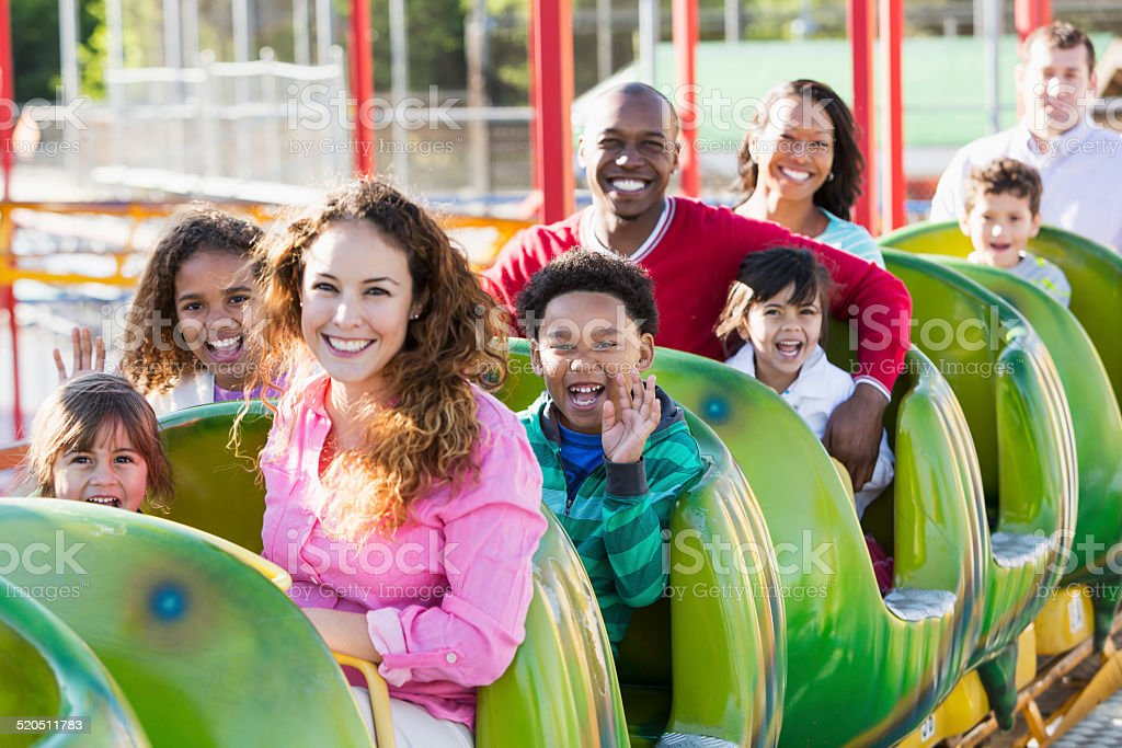 Multiracial group of people on rollercoaster ride stock photo