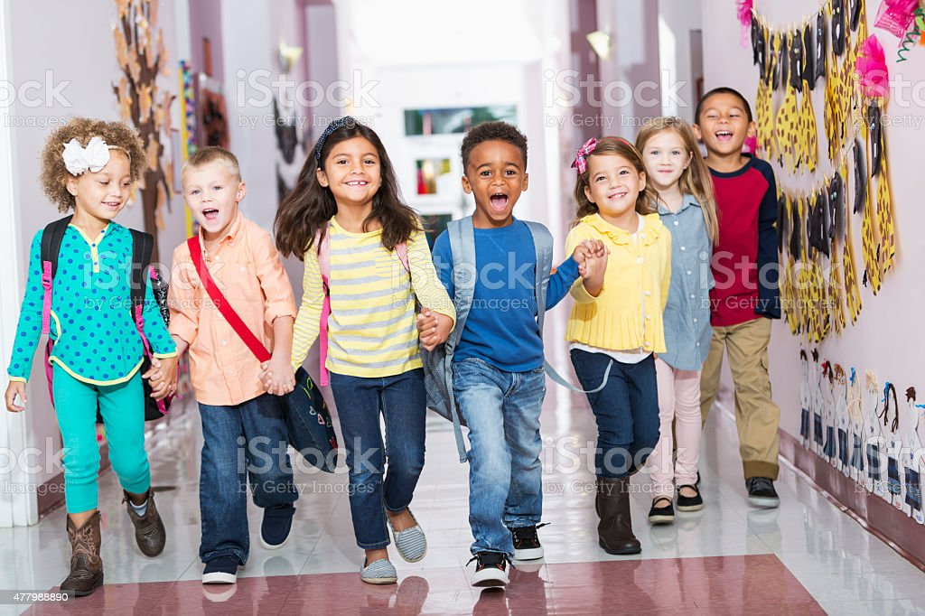 Multiracial group of preschoolers running down hallway stock photo