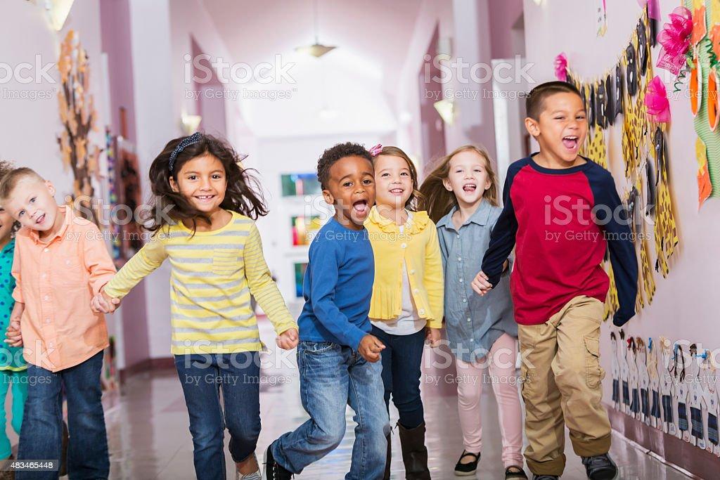 Multiracial group of preschoolers running down hallway stock photo
