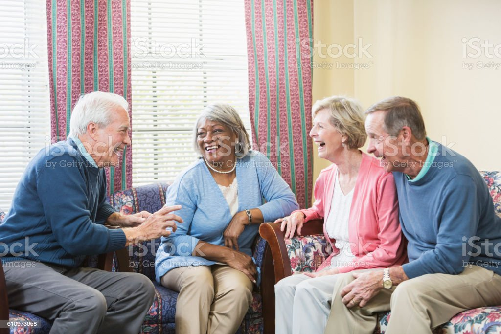Multiracial group of seniors sitting and talking stock photo