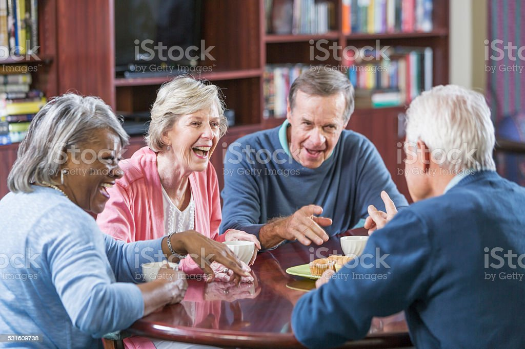 Multiracial group of seniors talking over coffee stock photo