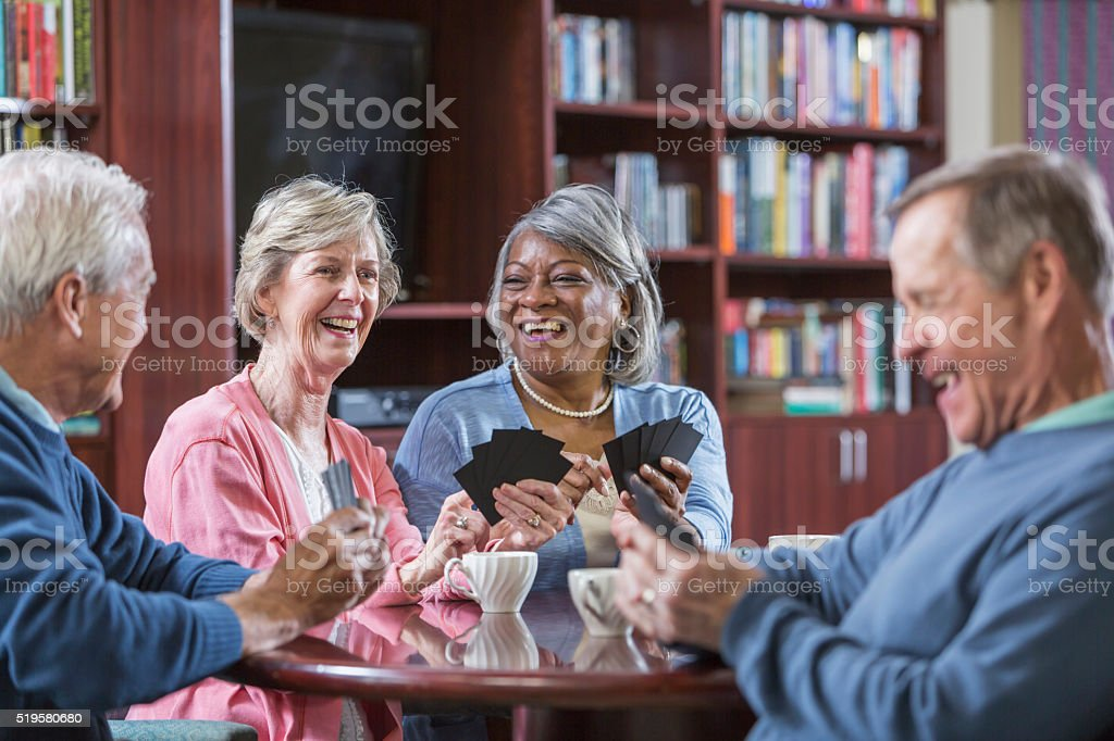 Multiracial group of seniors talking, playing card game stock photo