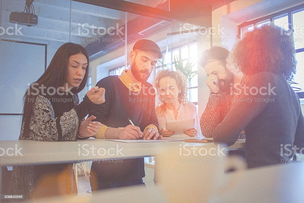 Multiracial group of young entrepreneurs gathered around work schedule stock photo