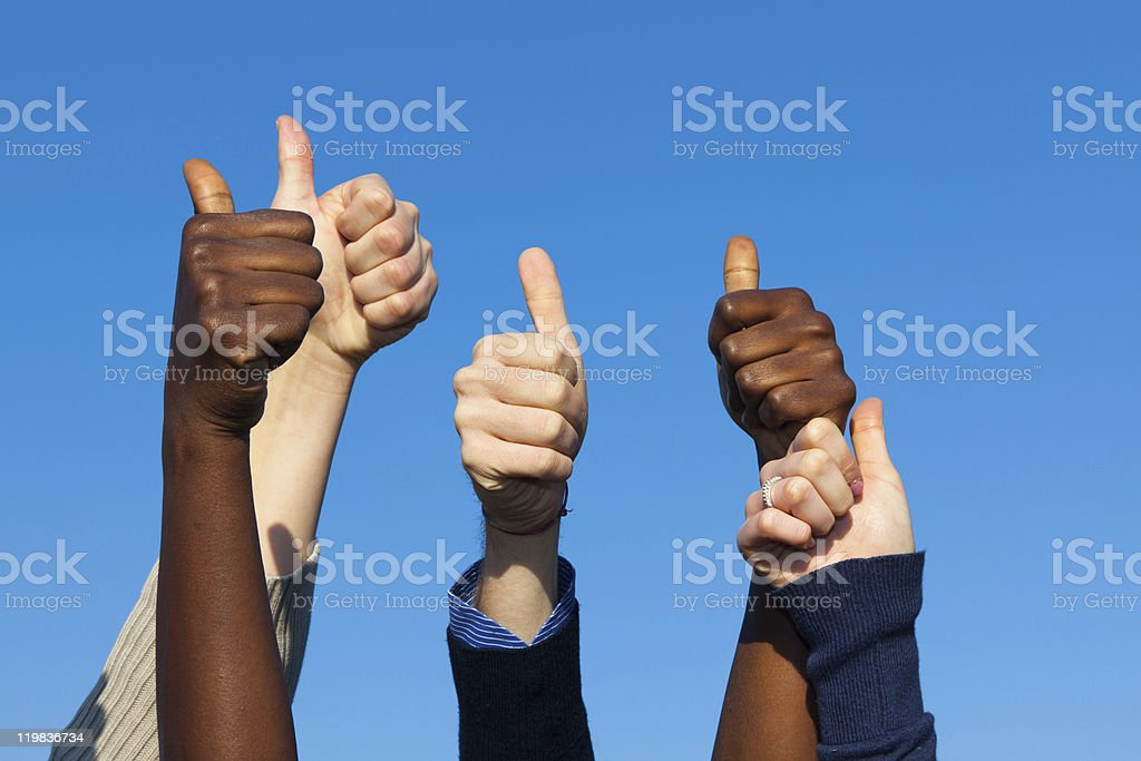 Multiracial hands with thumbs up raised against blue sky stock photo