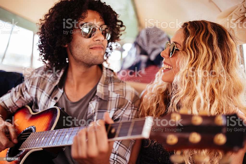 Multi-Racial Hipster friends Singing Together on road trip with guitar stock photo