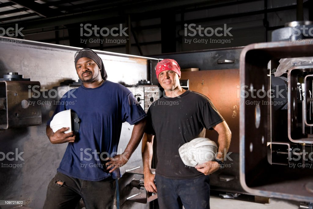 Multiracial industrial workers standing in factory royalty-free stock photo