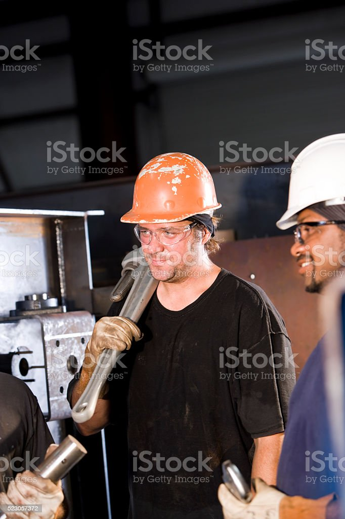 Multiracial industrial workers working in factory stock photo