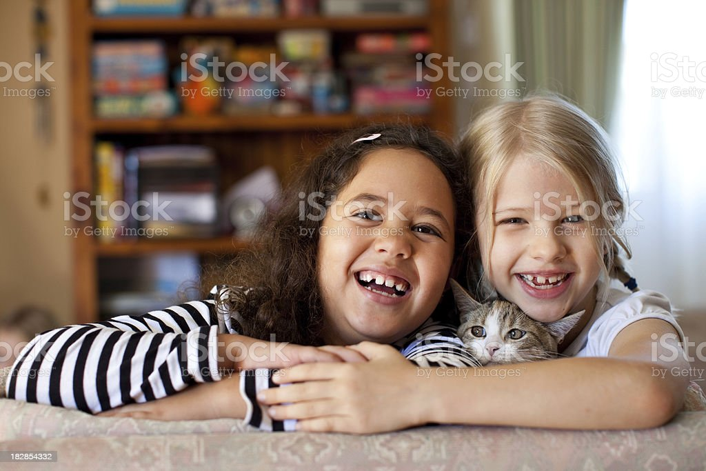 Multiracial Kids laughing indoors with pet kitten cat stock photo