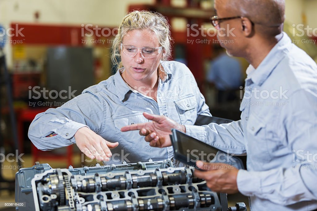 Multi-racial mechanics with engine and digital tablets stock photo