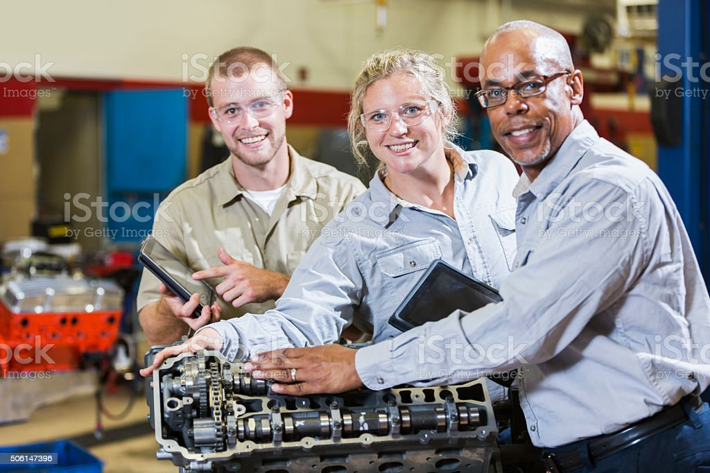 Multi-racial mechanics working on gasoline engine stock photo