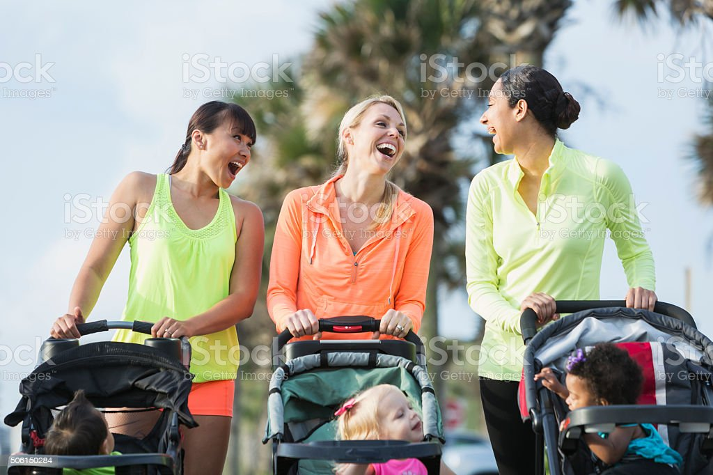 Multi-racial mothers with babies in jogging strollers stock photo