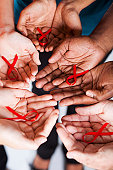 multiracial people holding red ribbon for AIDS HIV awareness