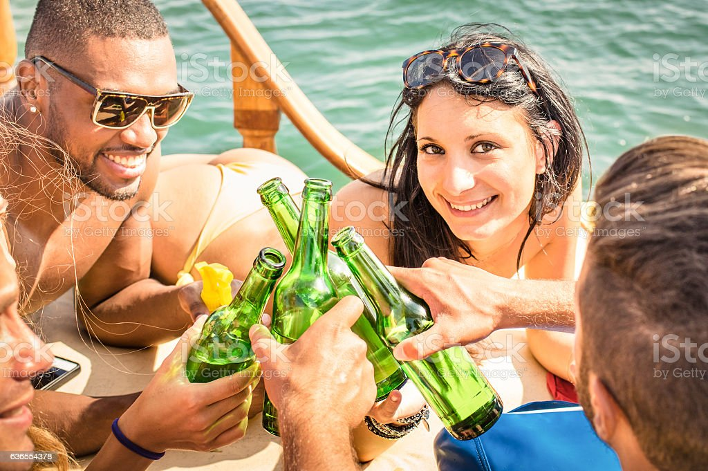 Multiracial people on yacht sailboat drinking beer and having fun stock photo
