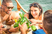 Multiracial people on yacht sailboat drinking beer and having fun
