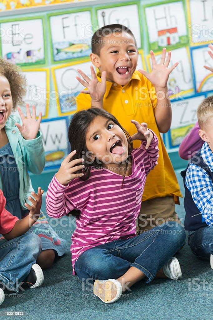 Multiracial preschoolers having fun making faces stock photo