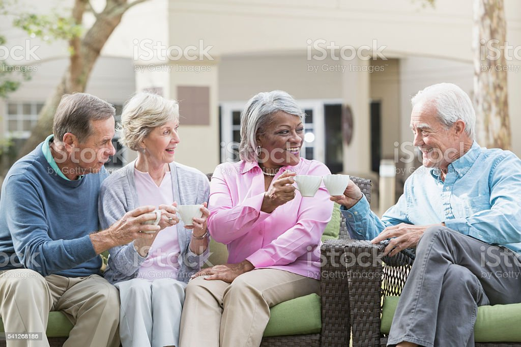 Multiracial senior friends outdoors drinking coffee stock photo