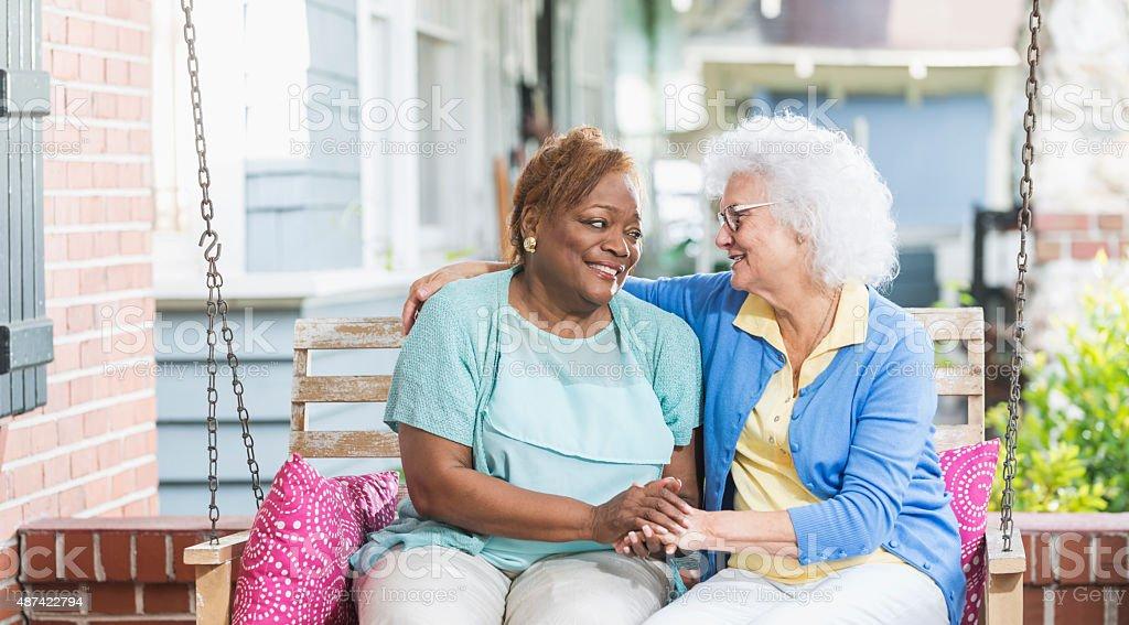 Multiracial senior women sitting on porch swing stock photo