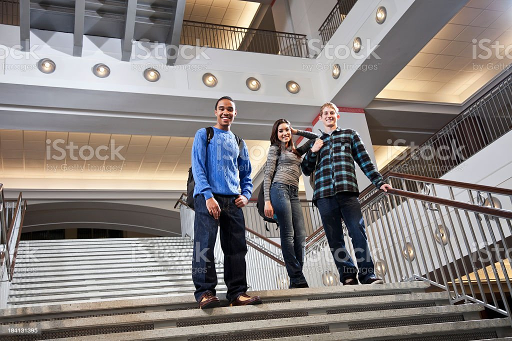 Multiracial students on steps of school building royalty-free stock photo