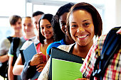 multiracial students standing in a row smiling