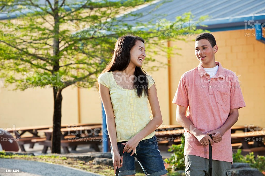 Multiracial teenage couple playing miniature golf royalty-free stock photo
