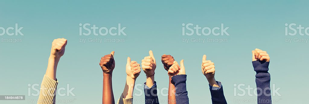 multiracial thumb up on the sky stock photo