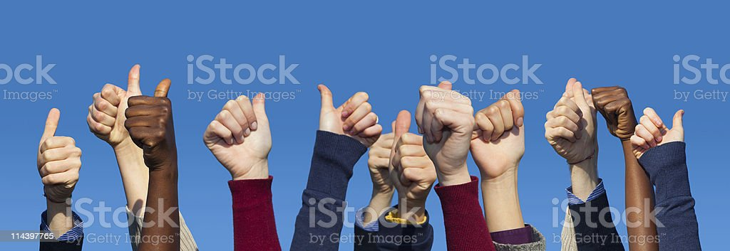 Multiracial Thumbs Up Against Blue Sky stock photo
