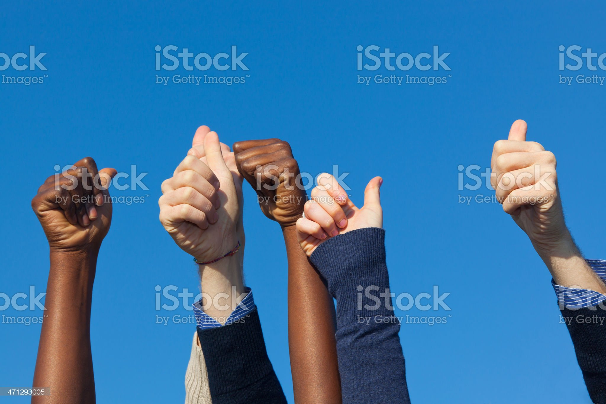 Multiracial Thumbs Up Against Blue Sky royalty-free stock photo