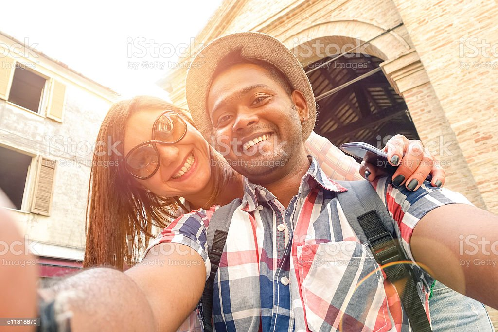 Multiracial travel couple taking selfie and having fun stock photo