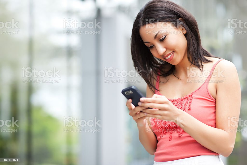 Multiracial woman texting on her cell phone royalty-free stock photo