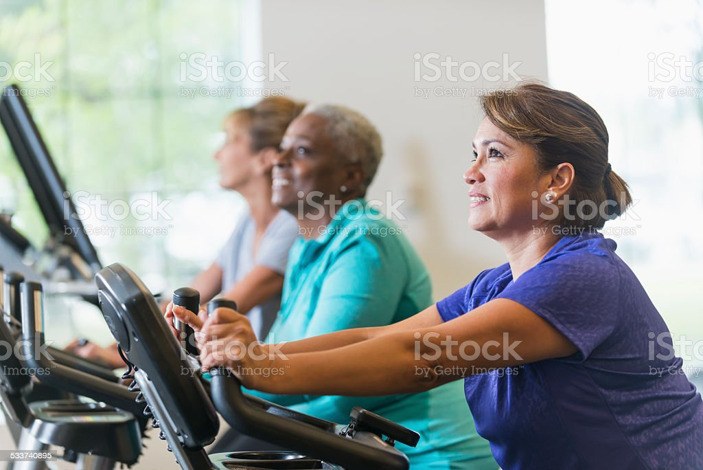 Multiracial women riding exercise bikes at gym stock photo