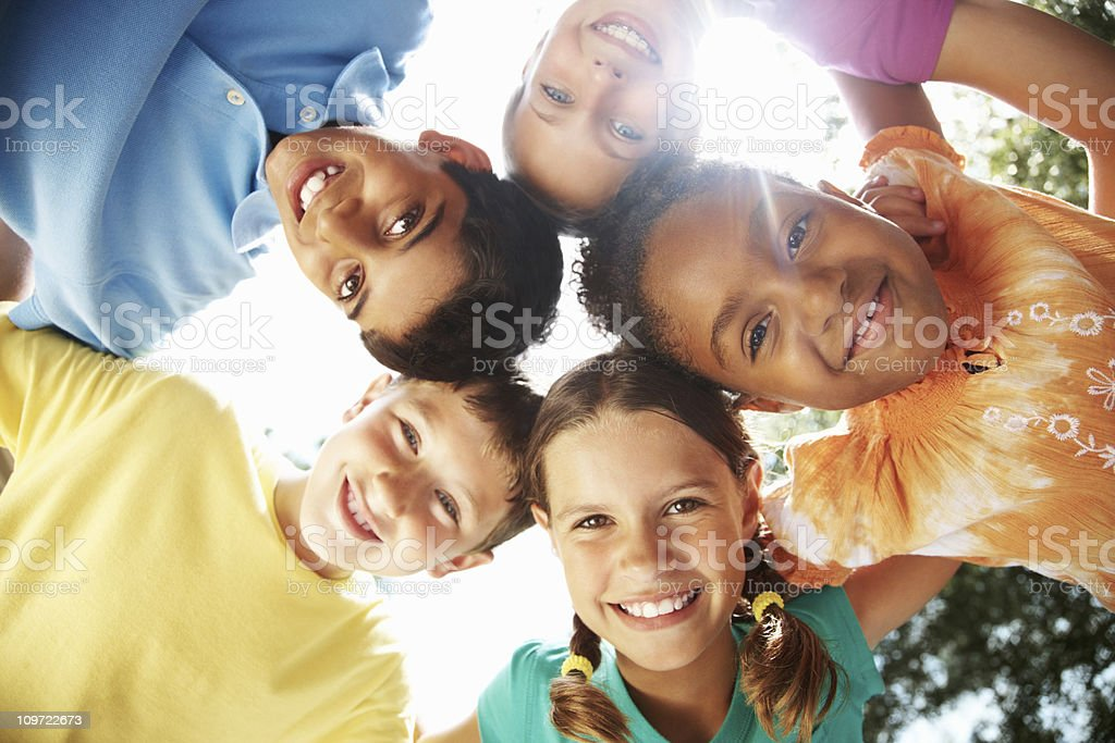 Multiracial young friends making a huddle against sky stock photo