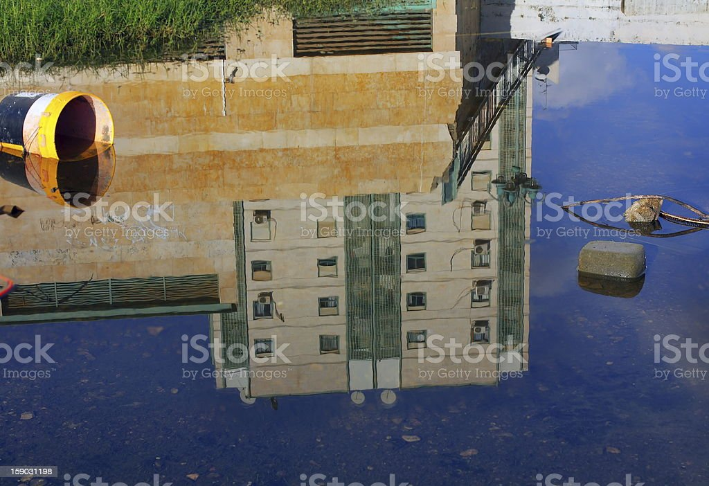 multistorey building reflected in puddle royalty-free stock photo