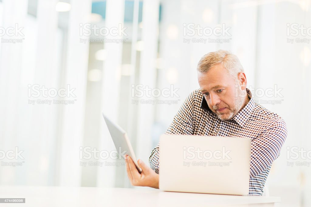 Multi-tasking businessman using wireless technology in the office. stock photo
