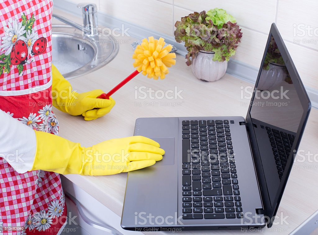 Multitasking concept. Woman with cleaning brush and laptop stock photo