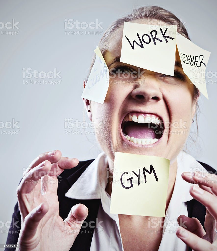 Multitasking gone mad! Overburdened woman covered in sticky  reminders royalty-free stock photo