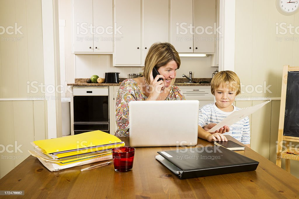 Multi-tasking mother at home with her son royalty-free stock photo