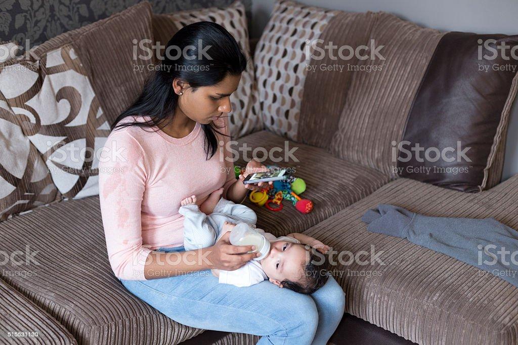 Multitasking mother on phone stock photo